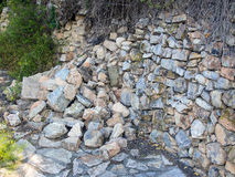 Collapsed Stone Wall. Traditional Greek loose rock wall, partly collapsed, rubble on path Royalty Free Stock Images