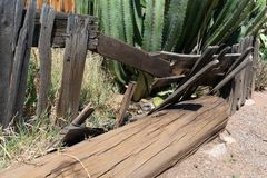 Collapsed wooden fence in front of an old abandoned building royalty free stock photography