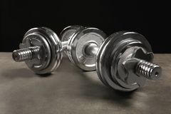 Collapsible dumbbells on grey textured surface against. Black background, closeup Royalty Free Stock Image