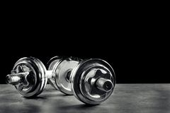 Collapsible dumbbells on grey textured surface. Against black background Stock Images