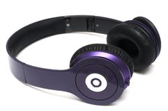 A collapsible purple wireless headphone. A photo taken on a collapsible purple wireless headphone against a white background Stock Photos