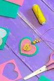 Collar agradable del colgante del corazón del fieltro Tijeras, hilo, hojas del fieltro y pedazos en un fondo de madera púrpura Id Fotos de archivo