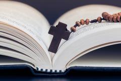Collar cruzado cristiano en el libro de la Sagrada Biblia, religión de Jesús concentrada foto de archivo libre de regalías