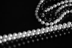 Collar de gotas blancos y negros en un fondo oscuro Rebecca 36 fotos de archivo libres de regalías