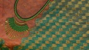 Collar de la joyería de la moda en el fondo de seda de la sari Foto de archivo libre de regalías