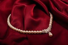 Collar de la perla en la materia textil roja Imágenes de archivo libres de regalías