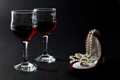 Collar de la perla y anillo de oro en joyero con dos copas llenadas del vino rojo aislado en negro Imagen de archivo