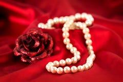 Collar de la perla y una rosa roja Imagen de archivo libre de regalías