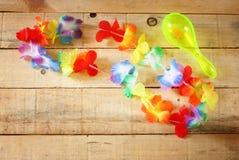 Collar de los leus coloridos brillantes de las flores en el fondo de madera imagen de archivo libre de regalías