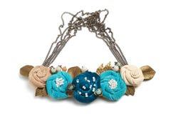 Collar hecho a mano bajo la forma de varias flores de colores ciánicos, azules y beige en un fondo blanco Fotos de archivo