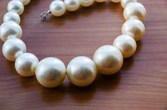 Collar hermoso, blanco pulsera hecha de beadson una tabla de madera fotografía de archivo
