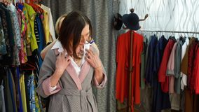 Collar que intenta de la mujer elegante en tienda de los accesorios Vendedor que ayuda a intentar el collar elegante en accesorio almacen de video