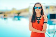 Collar y gafas de sol de la declaración de la mujer que llevan de moda por la piscina Foto de archivo