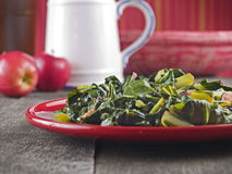 Collard greens & bacon. Collard greens and bacon on a red plate with apples and a water pitcher in the background Stock Images