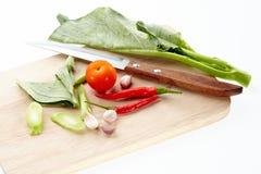 Collard, tomat, röd chili, vitlök och kniv på att hugga av kvarteret Royaltyfri Fotografi