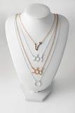 Collares en la forma del molelule y de la constelación Piscis hechos del oro y de la plata en el soporte blanco Accesorios de luj Imagen de archivo