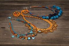 Collares moldeados hechos a mano de la joyería en la tabla de madera Fotos de archivo libres de regalías