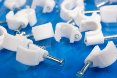 Collarini per cavi di plastica bianchi con i chiodi Immagine Stock Libera da Diritti