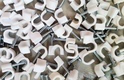 Collarini per cavi di plastica con i chiodi d'acciaio immagini stock