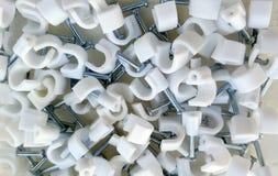 Collarini per cavi di plastica con i chiodi d'acciaio fotografia stock