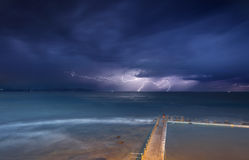 Collaroy storms and lightning. Views from Collaroy over the rockshelf and rockpool south of the beach towards the north east at the storms.  Seeking shelter from Stock Photography