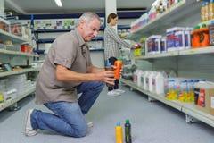 Colle de achat de client d'homme dans l'hypermarché d'articles de ménage photographie stock libre de droits