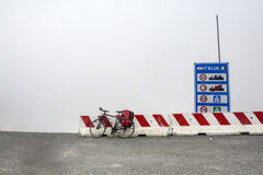 Colle dell'Agnello, Italian Alps: bicycle and fog. Top of Colle dell'Agnello (Italy-France): bicycle with red bags and fog Stock Images