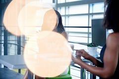 2 colleages обсуждая идеи используя таблетку и компьютер Стоковое Фото