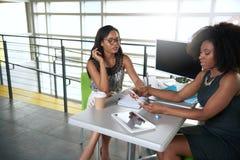 2 colleages обсуждая идеи используя таблетку и компьютер Стоковая Фотография RF