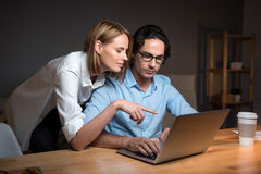 Colleague giving advice to her friend with the laptop. Royalty Free Stock Photography
