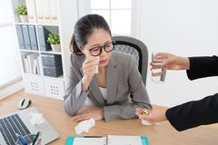 Colleague giving pills and water for painful woman Stock Image