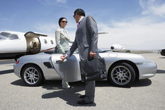 Colleague Holding Door Of Car For Colleague Near Private Aircraft. Businessman holding door of convertible for colleague on landing strip near private aircraft stock photos