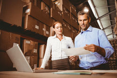 Colleague with laptop at warehouse Royalty Free Stock Images