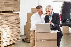 Colleague with laptop at warehouse Stock Photo