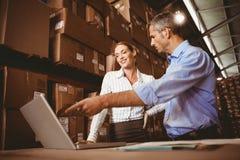 Colleague with laptop at warehouse Stock Photos