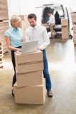 Colleague with laptop at warehouse Royalty Free Stock Photography