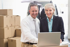 Colleague with laptop at warehouse Royalty Free Stock Photos