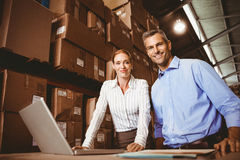 Colleague with laptop at warehouse Stock Images