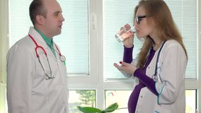 Colleague medic doctor give a pill and glass of water for pregnant woman stock video footage