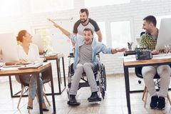 A colleague rolls a person in a wheelchair around the office. They have fun and laugh. Stock Photos