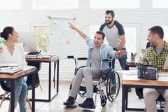 A colleague rolls a person in a wheelchair around the office. They have fun and laugh. Royalty Free Stock Photo