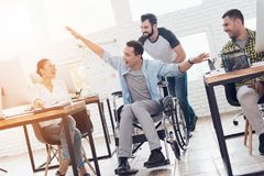 A colleague rolls a person in a wheelchair around the office. They have fun and laugh. Royalty Free Stock Photos