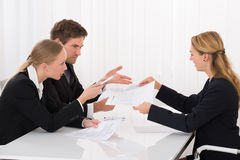 Colleague Showing Document To Businesspeople. Unhappy Female Colleague Showing Document To Young Businesspeople In Meeting Royalty Free Stock Image