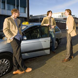 Colleague taxi drivers. Three taxi drivers haning around a cab during their break stock photo