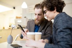 Colleagues analyzing information on smartphone in cafe stock images