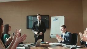 Colleagues applauding businessman in office stock footage