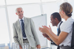 Colleagues applauding smiling manager during a meeting Royalty Free Stock Images