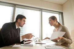 Colleagues arguing at workplace, disagree about document, error. Side view of colleagues arguing at workplace, executives disagree about papers, found error in stock image