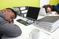 Colleagues asleep at their respective desk stock photo
