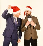 Colleagues with beards argue about business. Christmas celebration. At work concept. Men in smart suits and Santa hats isolated on white background. Businessmen royalty free stock image